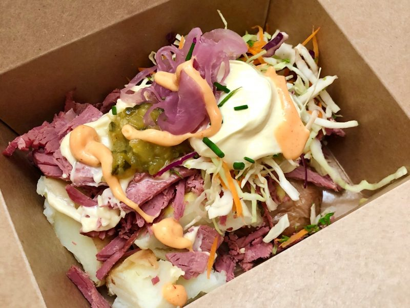 potato topped with corn beef, slaw, zucchini relish, pickled onions, cheese sauce and sour cream
