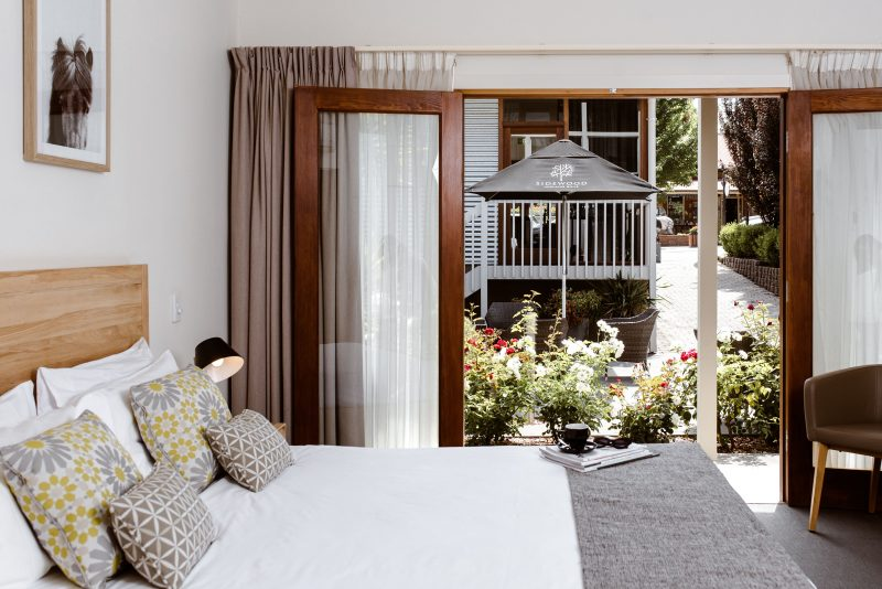 A king-sized bed with Scandinavian-style furnishings, overlooking a garden
