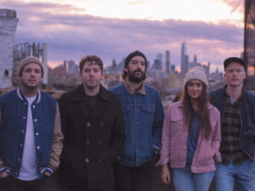 Image of The Paper Kites standing against a city skyline