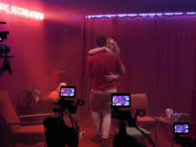 A woman embraces a man in front of cameras