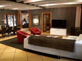 LOUNGE AREA , WOOD FIRED HEATER, L-SHAPED LOUNGE , SWIVEL CHAIRS, COFFEE TABLE, H/ DEF 65' OLED TVT