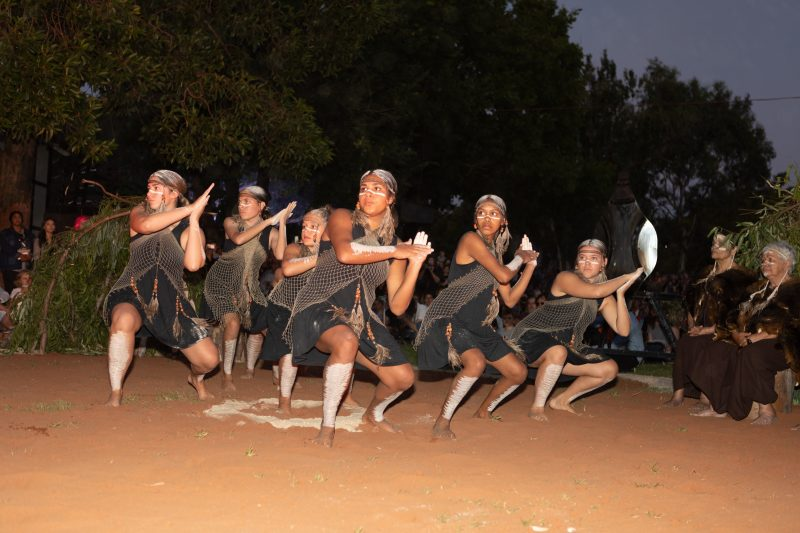Seven Yellaka dancers performing on sand in traditional dress at sunset