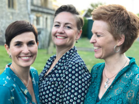 Image of the three women standing together, smiling and laughing
