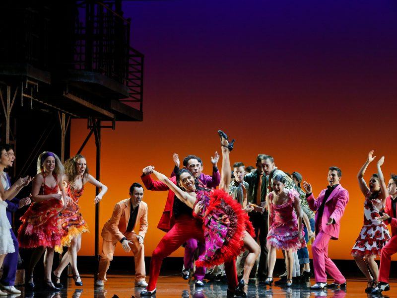 West Side Story - dancers on stage gather around a man and woman, the woman is kicking her leg high