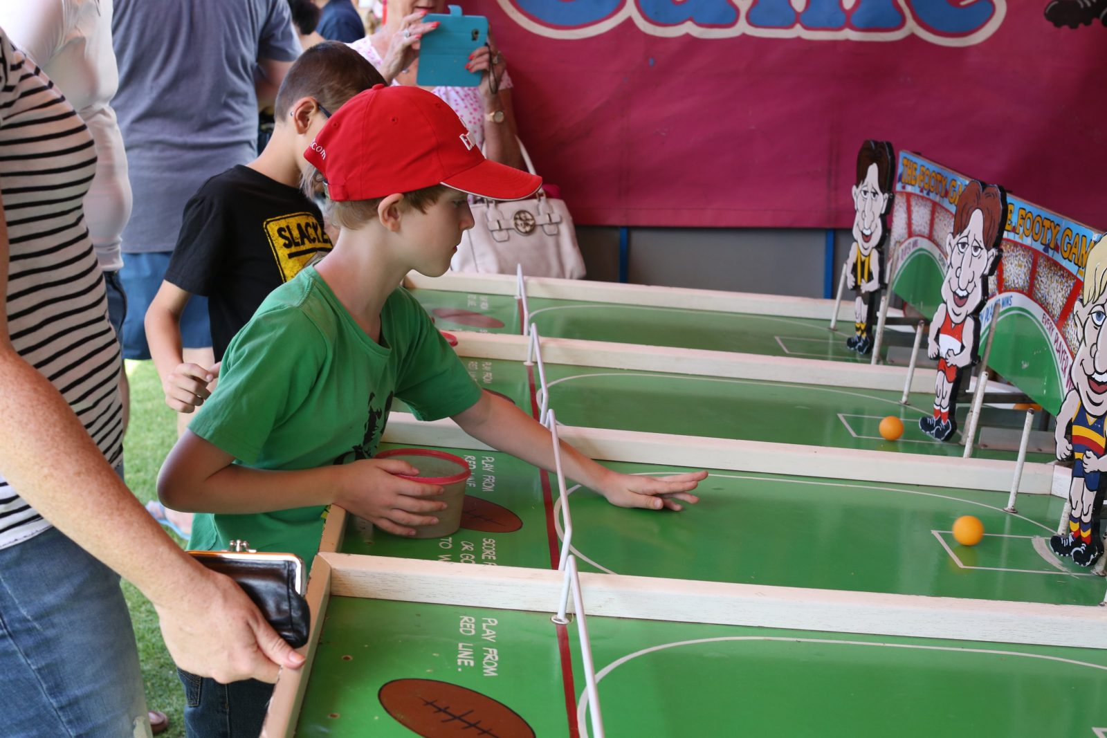 A boy in a green shirt and red hat plays a ball rolling game