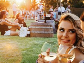 A woman enjoys a glass of wine on the lawns at Wirra Wirra