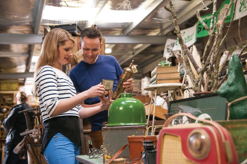 A man and a woman looking at an assortment of vintage and antique wares