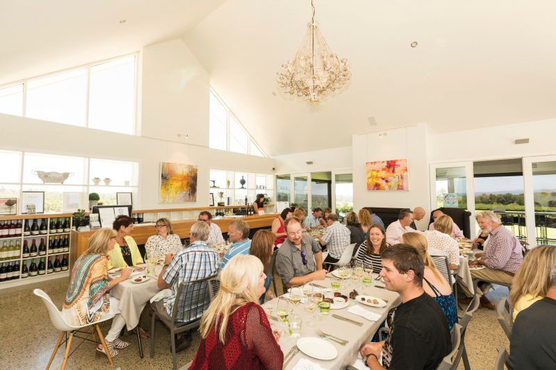 About 25 people seated in small groups at tables set for dining, in the Artwine cellar door