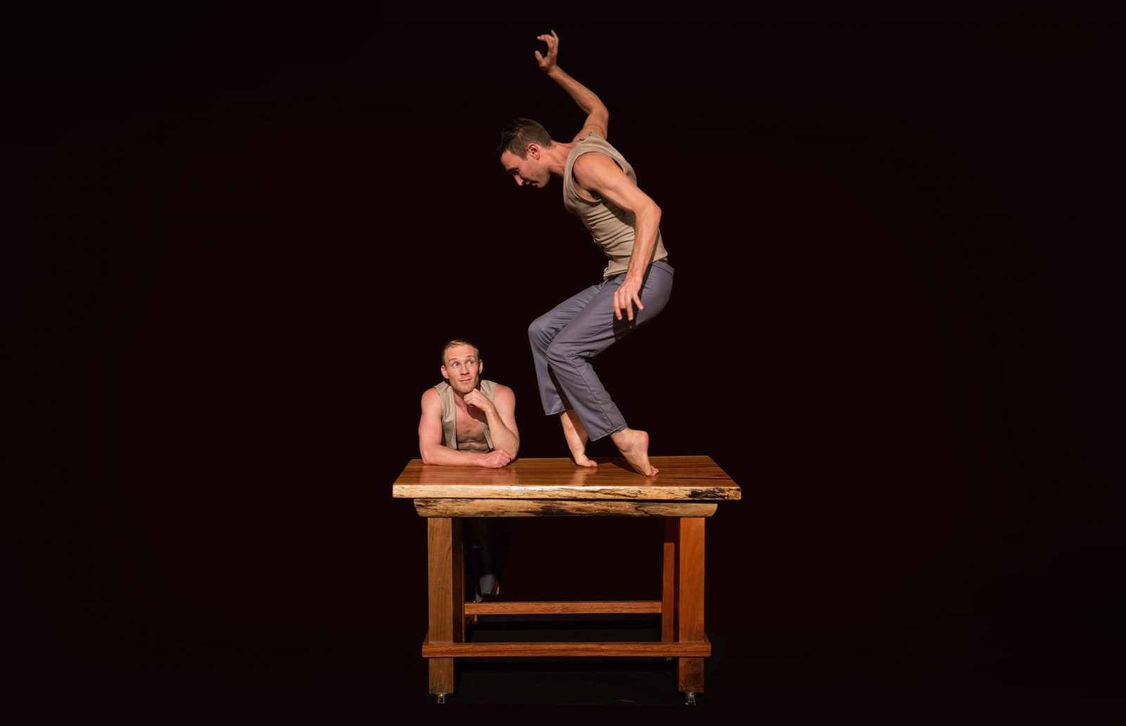 An acrobat balances on his toes on a table. Another acrobat leans on table looking up at his partner