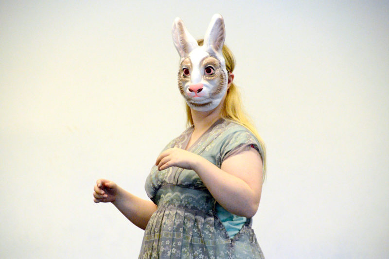 A woman stands with a rabbit mask covering her face