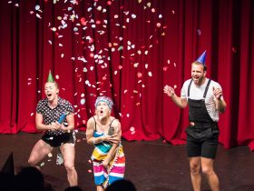 Confetti is falling down over 3 acrobats, 2 in party hats with their mouths wide in excited screams.