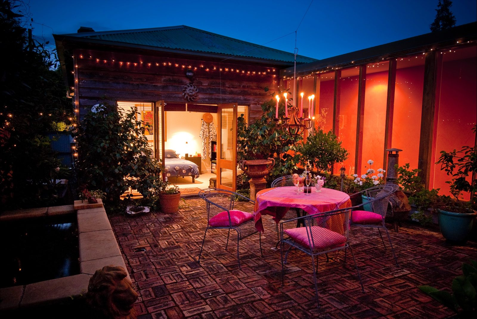 Private courtyard with warm glow of the chandelier and tinkling sounds of the fountain