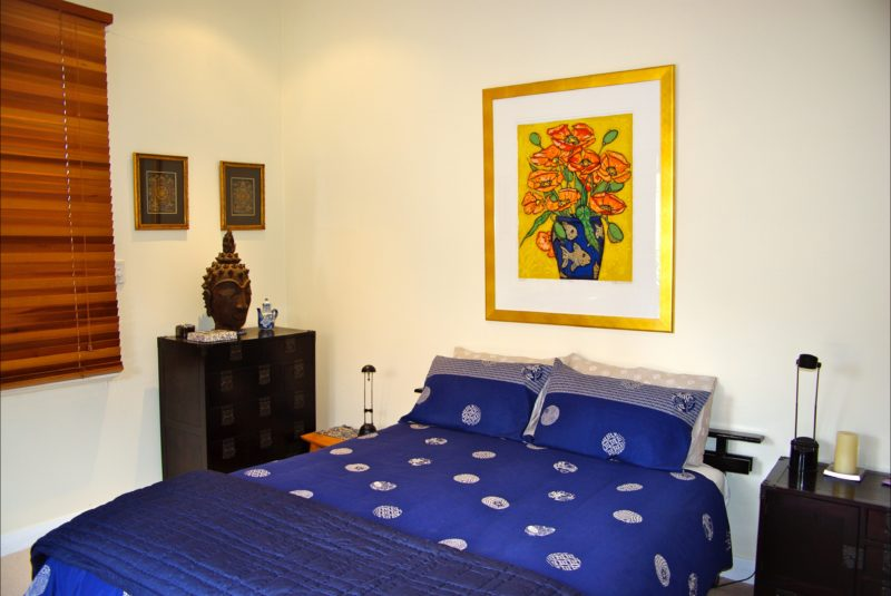 Queen size bedroom with original artwork and fine linen