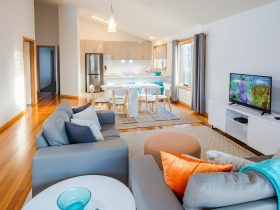 Main living area: two couches and pouffe, TV, dining table with six chairs, kitchen area at rear.