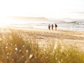 Couple walking along neck beach, Bruny Island