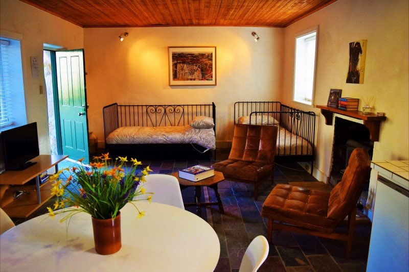 The Cottage living area with wood fired heater, two day beds and trundle bed and the TV/DVD.