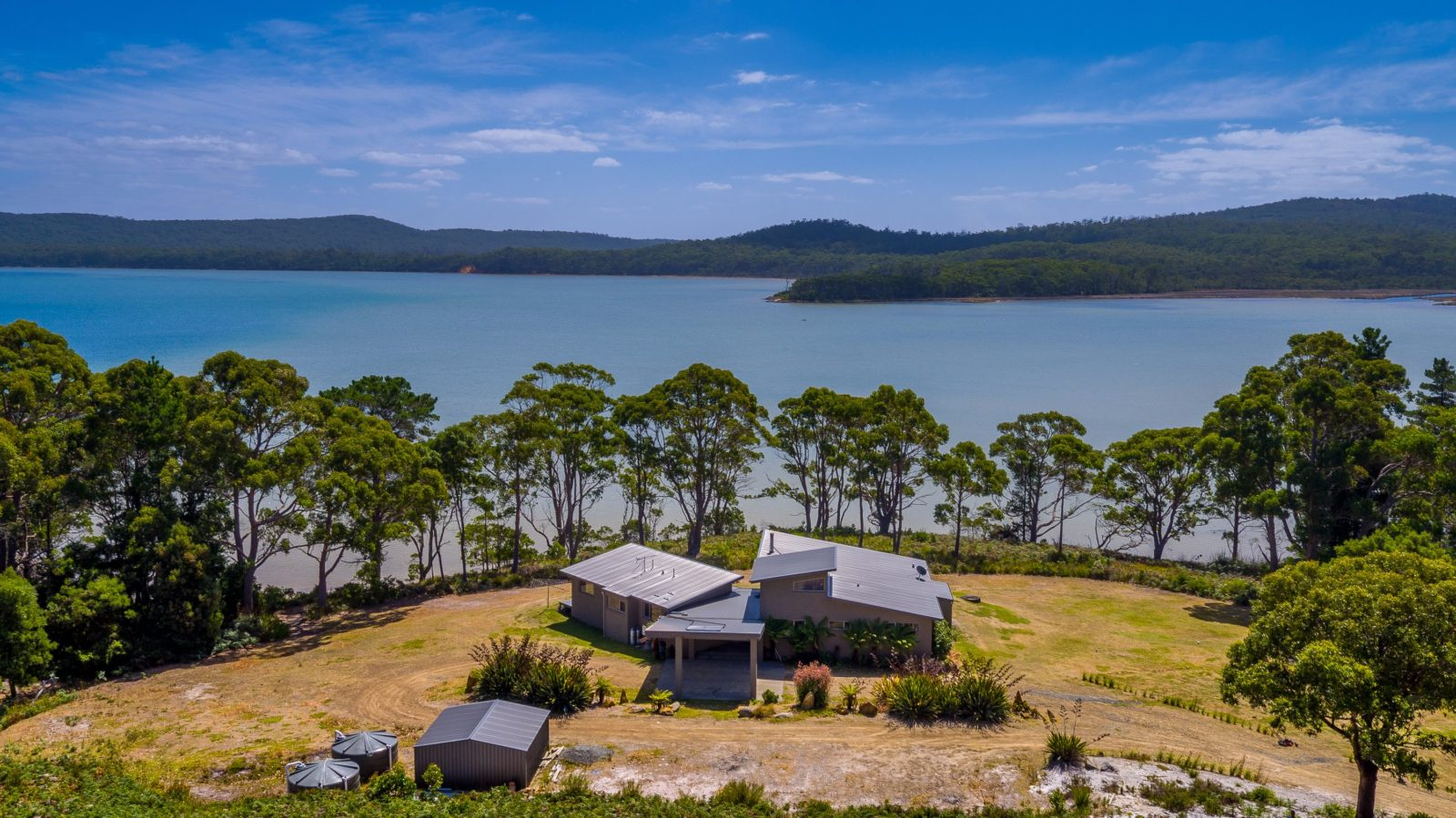 Cloudy Bay Lagoon Estate aerial view of house out to Cloudy Bay Lagoon on a sunny day