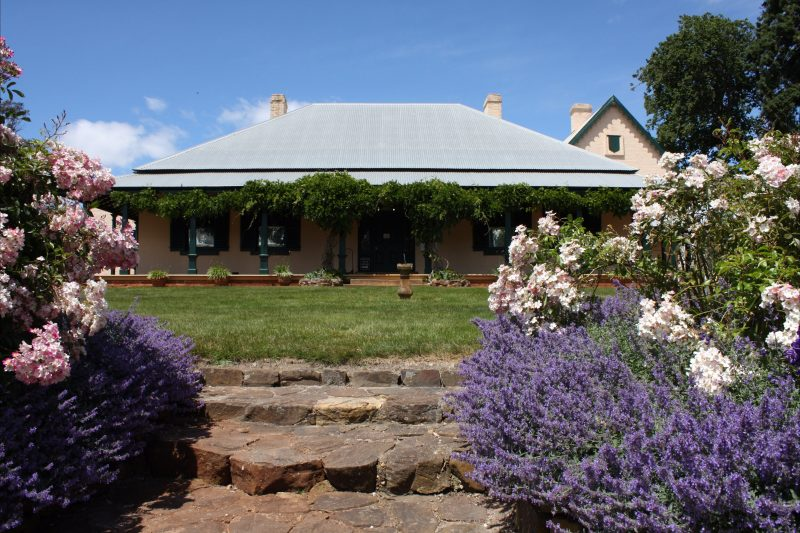 Cream, historic house, facing front door, with flowers blooming in the foreground.