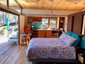 Free Spirit Pod living area and bifold door opening onto vast timber deck.