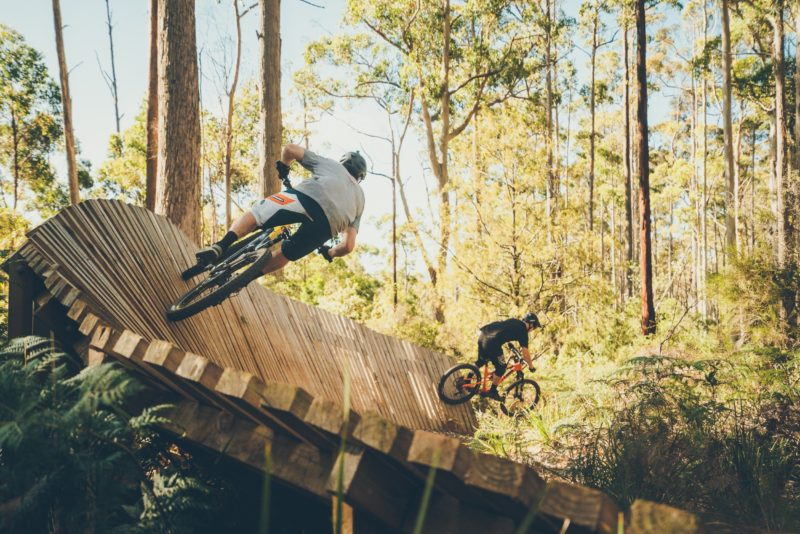men riding mountain bikes on wooden obsticles