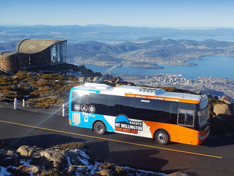 Bus parked at the summit of the mountain with panoramic views of the city below.