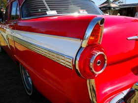the rear end of a restored vintage car, car with rear rins, red with white strips