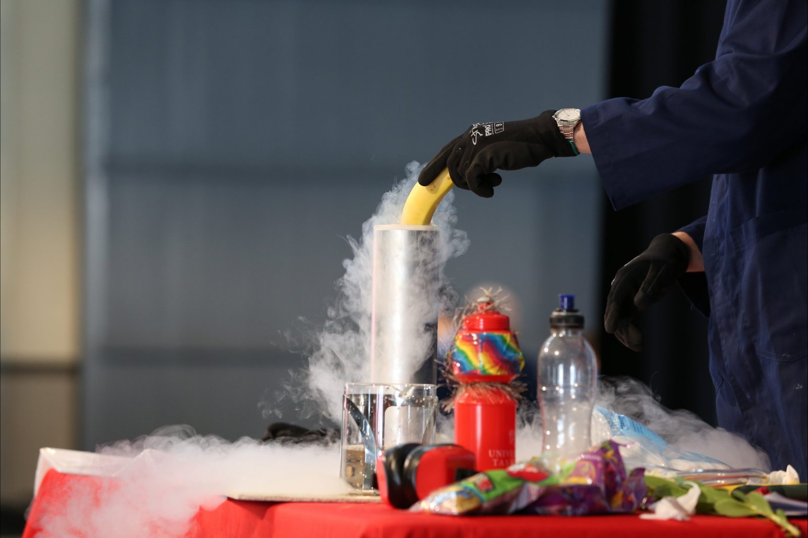 A man dipping a banana into liquid nitrogen.