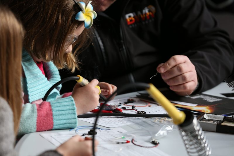 A man shows a little girl how to solder electronics