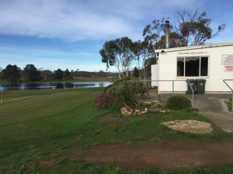 A shot of the club house and practise green with the lagoon in the distance