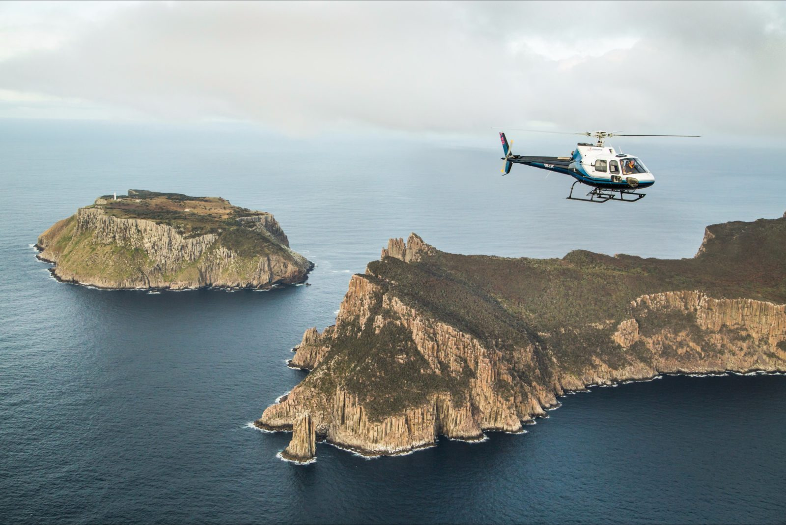 An Osborne helicopter flying above Cape Pillar with Tasman Island in the background