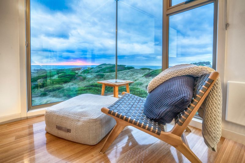 relaxing setting of bedroom lounge chair and ottoman with panoramic views of ocean and nature