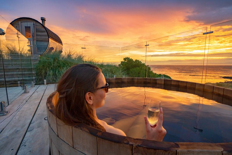 woman relaxing in timber hot tub with glass of champagne while looking at ocean