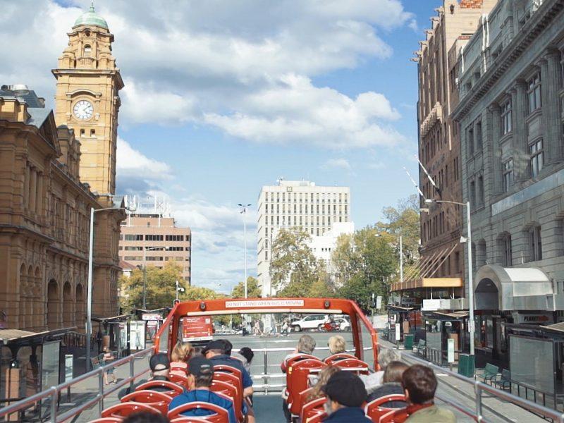 Double decker bus driving past historic buildings.