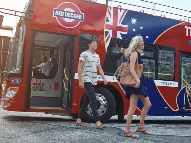 A young couple hop-off a double-decker bus.