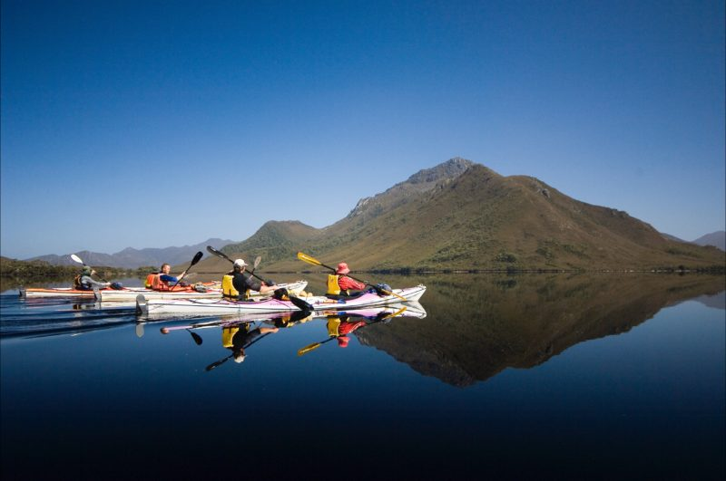 Kayakers paddling in perfect reflections in Southwest Tasmania
