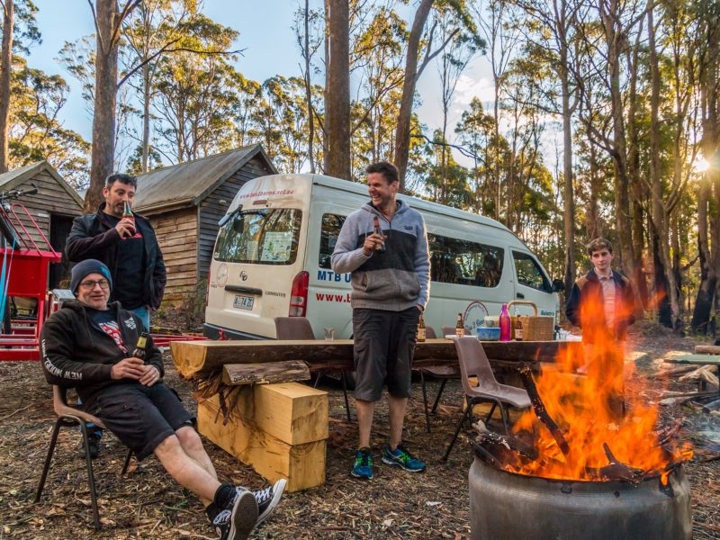 Three MTB riders standing near a fire pit and BBQ outside the Settlers Hut near Derby