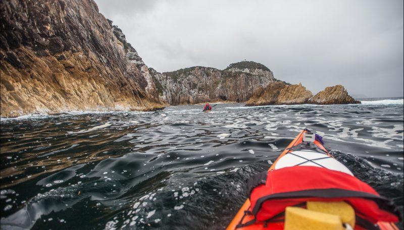 Sea kayakers paddling outside the Breaksea Islands on Port Davey in Southwest Tasmania