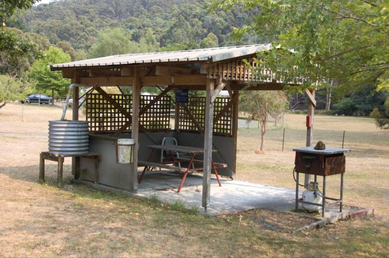 covered area with barbecue, table and seating