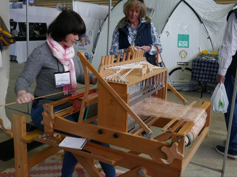 Exhibitor displaying weaving at Tasmanian Craft Fair