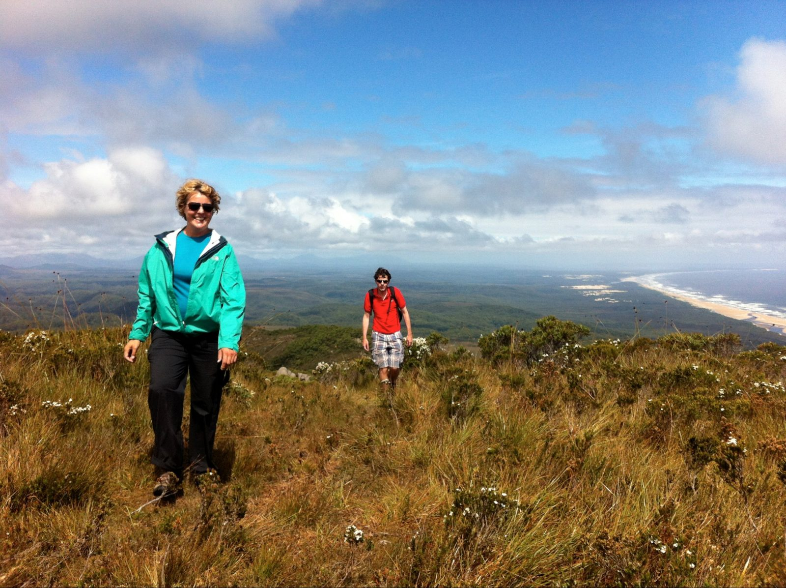 Two people walking up a button grass hill with views to Ocean Beach behind them. West Coast Tasmania