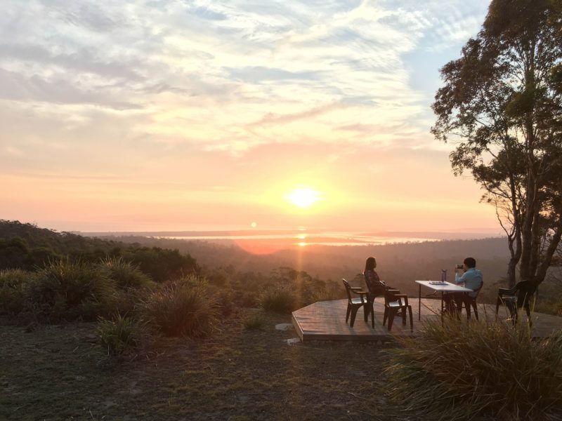 Guests enjoying a sunset view from a comfortable camp