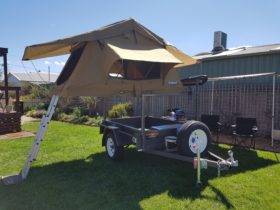 Rooftop camper setup with camping pack including foldup table, chairs and cooking utensils