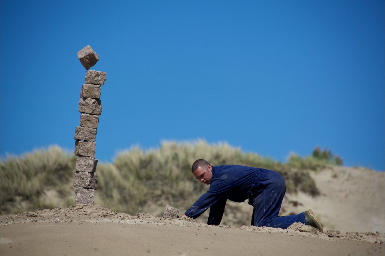 Nick Steur kneels on the ground at a beach location, with a stack of rocks in the background.