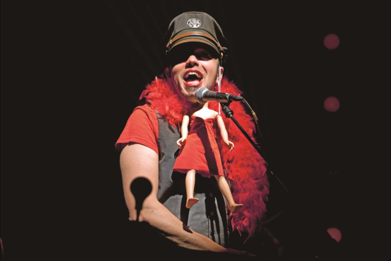 Hawksley Workman in flamboyant costume performs on stage.
