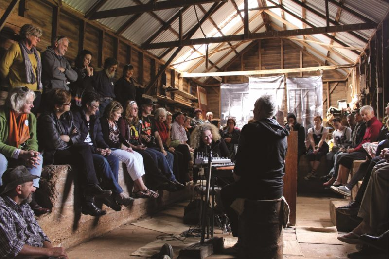 Audience sits around inside perimeter of a shed, rimming two performers and electronic instruments.