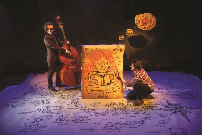A double bass player and cartoonist, drawing on large paper, on stage.