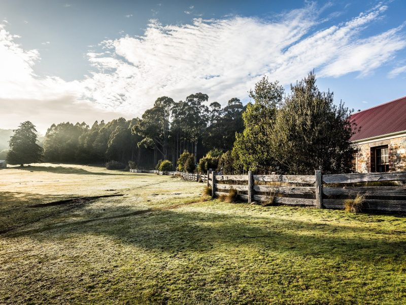 Chintock stone cottage with view across a green paddock, Tin Dragon Cottages, Tasmania
