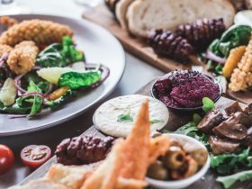 Close up image of food platters with olives, pickled foods, dips and crackers, and fried squid salad