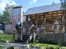 A man walking up the steps of an old cabin
