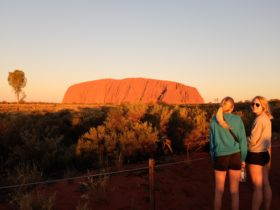 Travellers enjoy the sunset at Uluru